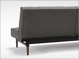 Schlafsofa Walton als Sofa aufgeklappt im Webstoff Grau mit gebeizten Füßen aus dunkler Ulme.