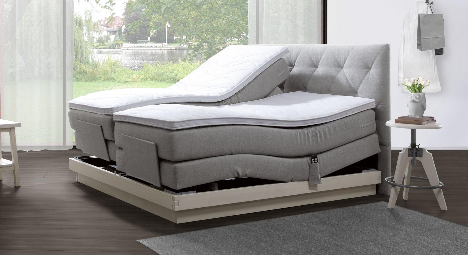 Boxspringbett Fremont mit elektrischer Verstelllung, hellgrauem Stoff und in Buche weiß.