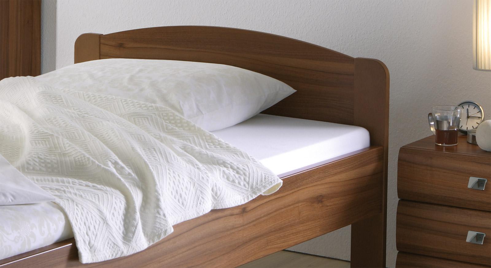 Schlichtes Bett San Martino mit massiv gerundetem Kopfteil.